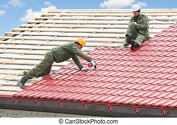 roofing work with metal tile - two workers on roof at works ...