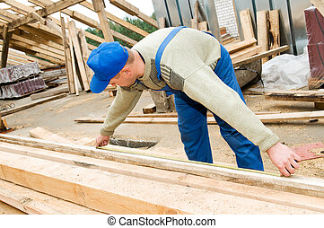 roofing works with measuring tape - builder worker at...