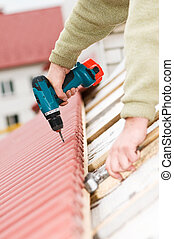 roofing works with screwdriver - Hands of builder worker at...