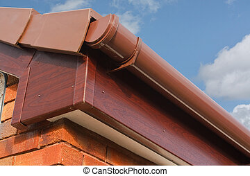 close up of Brown wood effect PVCu or plastic soffit, fascia and guttering on modern new build residential property