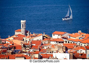 Roofs of a typical Mediterranean town and a sailing boat