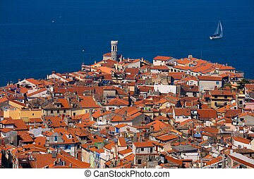 Roofs of a typical southern European town and a sailboat