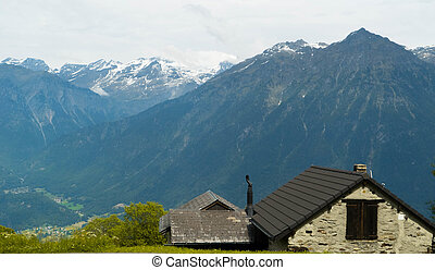 Roofs of houses on a background of beautiful and big mountains in the alpine mountains of Switzerland.