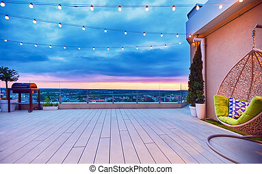 rooftop deck patio area with hanging chair on a sunset