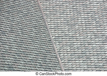 The grey shingles on a large rooftop