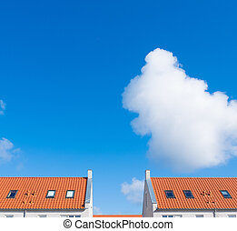 rooftop with orange tiles - rooftops against a cloudy sky in...