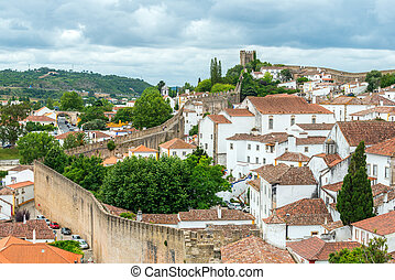 Rooftops, houses and old city wall with tower, Obidos (Portugal)