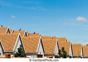 Row of condominium rooftops against blue sky.