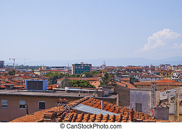 View of red old rooftops of a city under blue cloudy sky
