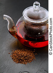 Rooibos tea, dry leaves and a small glass teapot brewing, on...