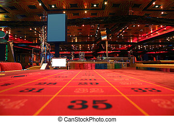 room in casino with red table for roulette game, view from table