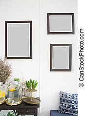 Room interior with frames on white wall