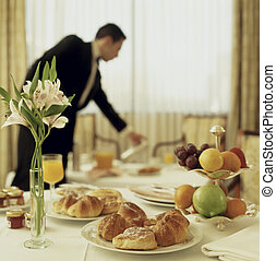 Big Hotel room service continental breakfast with waitress out of focus