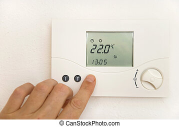 room thermostat - hand adjusting temperature at thermostat