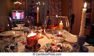 Room with decorated christmas dining table with bottle, glasses, candy, candles