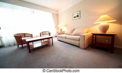 Room with lamps on each side of bed and pair of armchairs at table