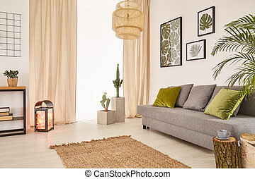 Light room with grey sofa, green pillows, carpet and window