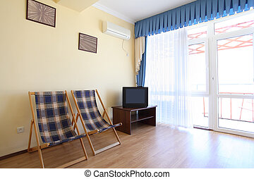 Room with two chaise lounges and  TV