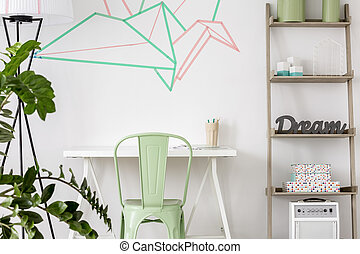 View of white desk with mint chair and decoration made with washi tape on the wall