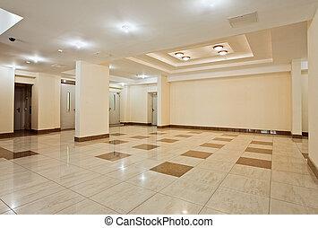 Roomy hall of modern residential building in beige tones
