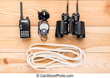 rope and navigation equipment for a complex and dangerous hike into the mountains, top view close-up on a wooden background