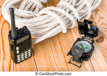 rope and navigation equipment for a complex and dangerous hike into the mountains,on a wooden background