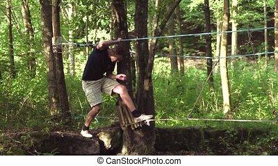 Rope Bridge - Young man walking carefully over a rope bridge...