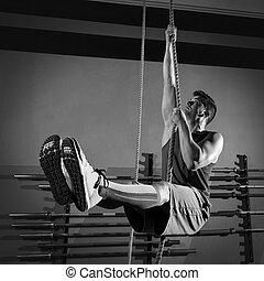 Rope Climb exercise man workout at gym climbing