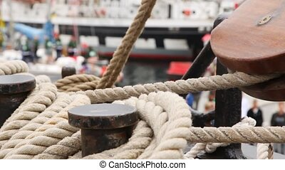 Rope for mooring lies collected on ship deck against walking...