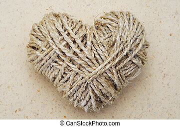 rope heart - heart-shaped coil of rope on a textured...