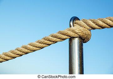 rope on metal pole, railing of beach walkway