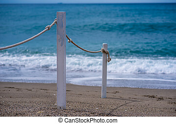 rope railing leading to calm sea, mediterranean beachscape,...