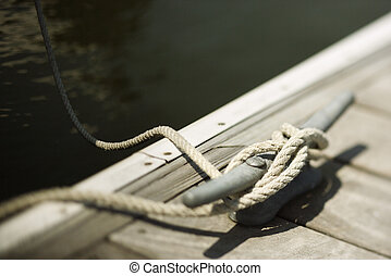 Rope tied to boat dock. - Rope tied to cleat on boat dock.