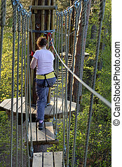 Young girl on high wire forest adventure course of rope bridges, Swings and slides