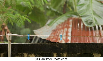 Rope with clothespins under heavy rain. Phuket island,...