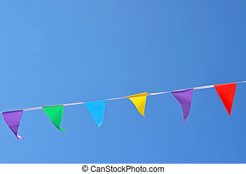 Rope with colored flags hanging on a blue sky background