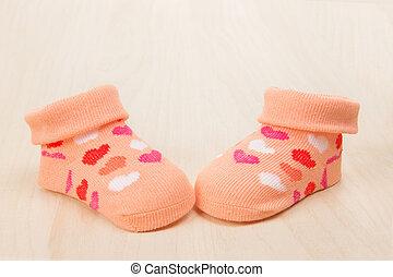 rosa, bebé, calcetín, con, corazones, en, un, de madera, plano de fondo