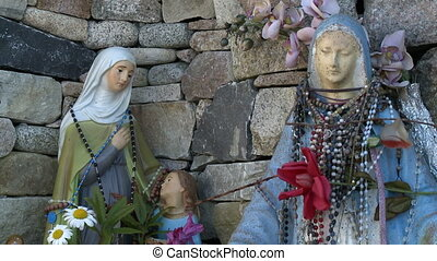 Rosaries Wrapped Around Statues Of Mary