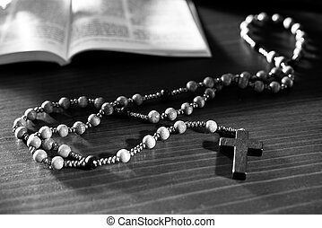Rosary and bible on the wooden table. Black and white.