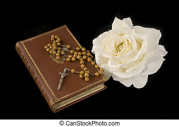 rosary and bible with white rose on black