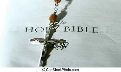 Rosary beads falling onto first page of bible in slow motion