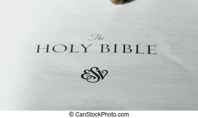 Rosary beads falling onto first page of holy bible in slow...