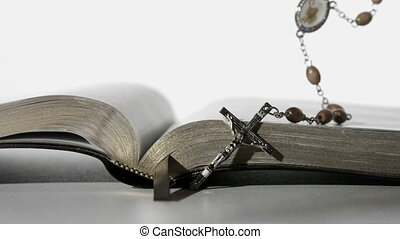 Rosary beads falling onto open bible on white background...