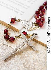 Rosary beads on a book of psalms and sandstone background
