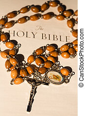 Rosary beads on page of bible - Silver and wooden rosary...