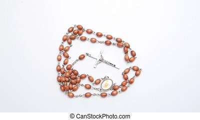 Rosary beads on white surface revolving video