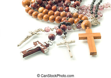 Rosary beads over white with focus on crosses