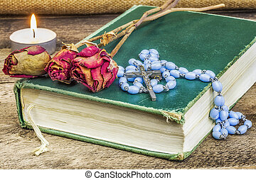 Rosary, bible, rose on the table