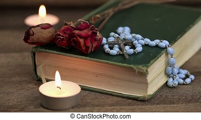 Rosary, bible, roses and candles on the table