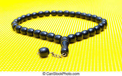rosary prayer beads on yellow background